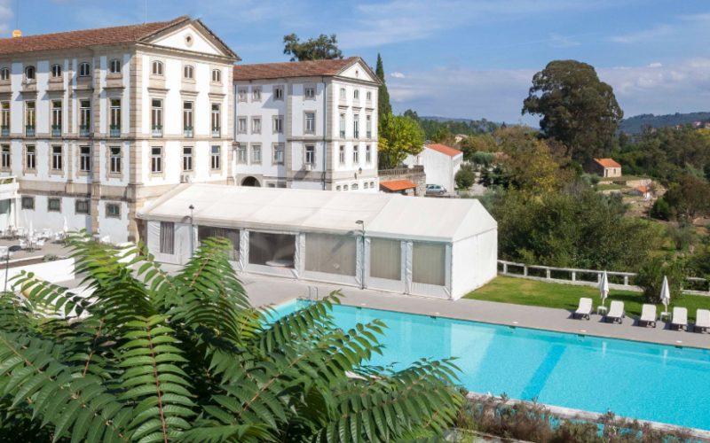 Hotel em estilo oitocentista, com grande piscina em frente, rodeado pela natureza